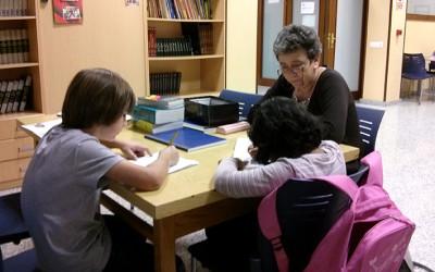 Una voluntaria da apoyo escolar en el Alojamiento Alternativo de Cocina Económica